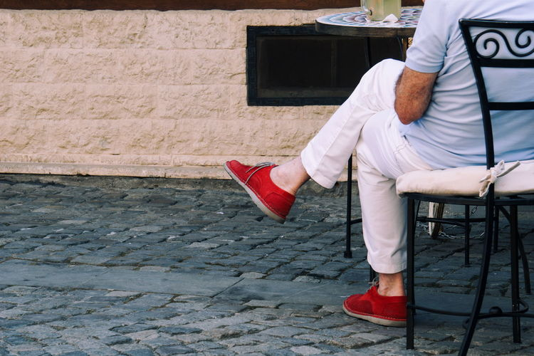 Low section of man wearing red shoe sitting on chair at sidewalk cafe