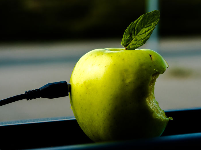 Close-up of charger and green apple at window