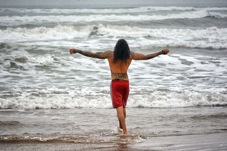 Rear view of shirtless man with arms outstretched wading in sea