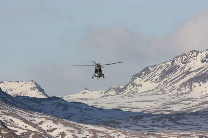 Helicopter Over Snowcapped Mountain Against Sky