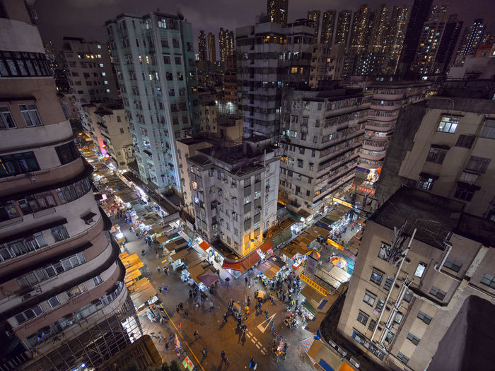 High angle view of illuminated street amidst buildings in city