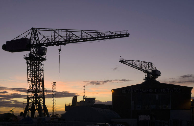 Low angle view of crane at construction site during sunset