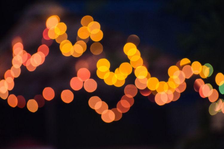 Defocused image of illuminated christmas lights against sky at night