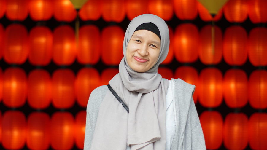 Portrait Of Smiling Woman In Hijab Against Red Decoration