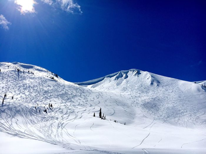 Low Angle View Of Ski Tracks On Snowcapped Mountains Against Blue Sky