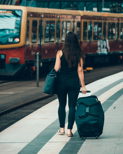 Rear view of woman walking at railroad station