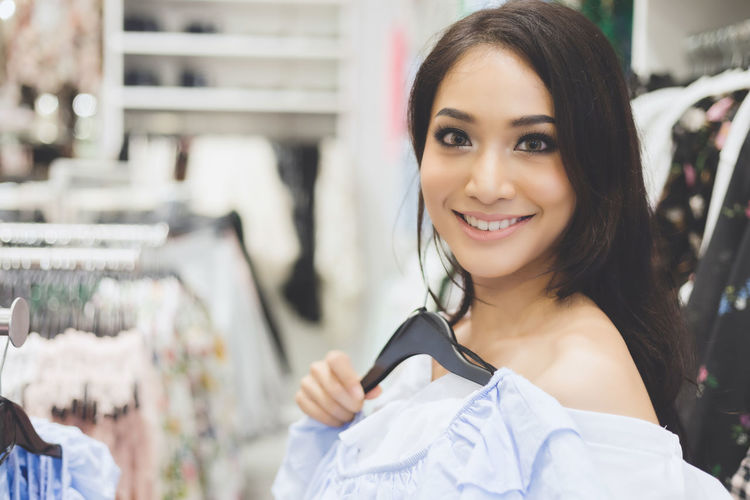 Portrait Of Smiling Young Woman Holding Cloth At Store