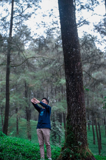 Man stretching hands while standing by trees in forest