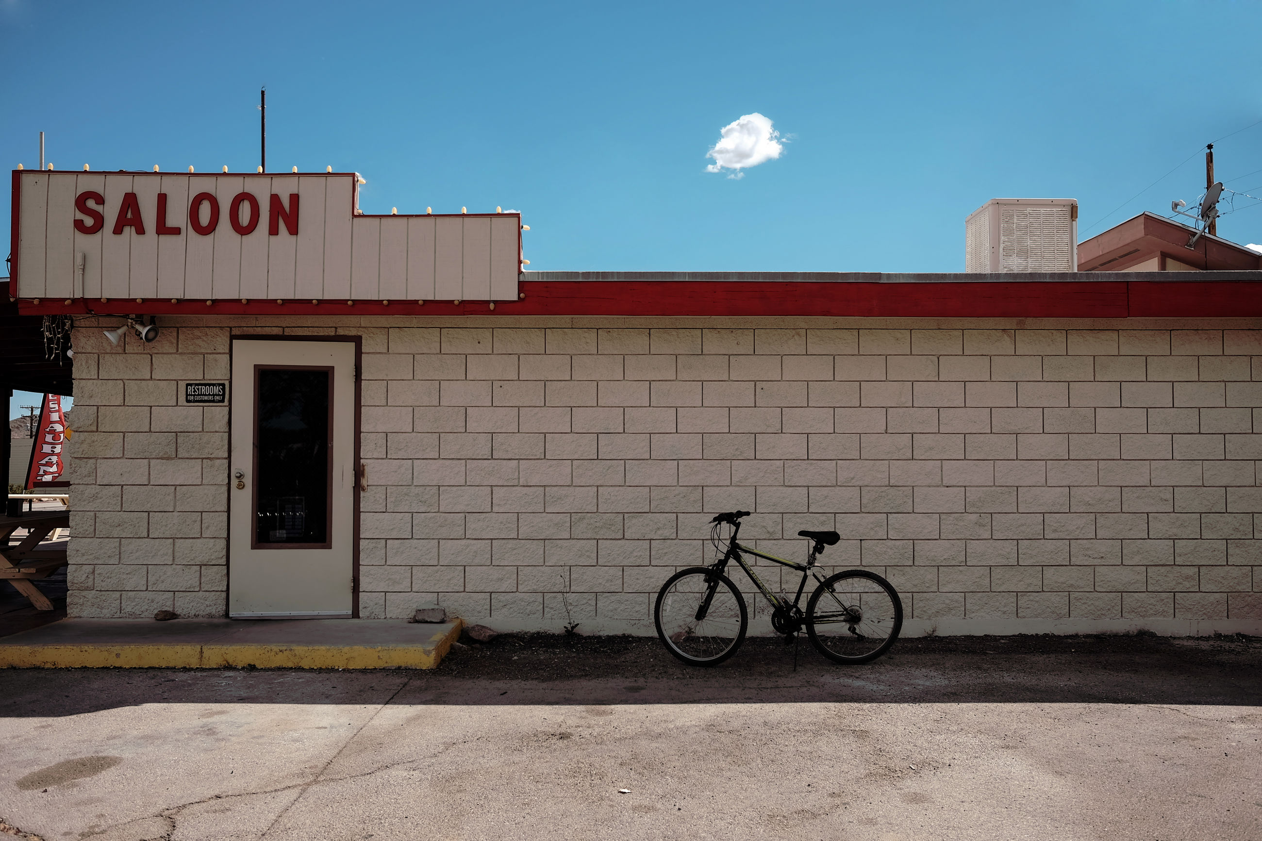 bicycle, architecture, building exterior, built structure, outdoors, text, transportation, day, sky, no people