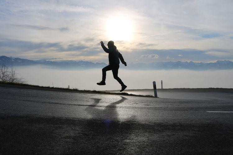 Full length of silhouette man jumping on road against sky