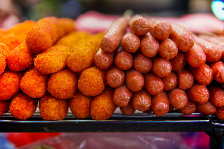 Close-up of fried hot dogs and nuggets for sale at market stall