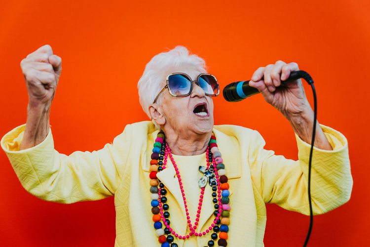 Senior woman wearing colorful jewelry and sunglasses singing against red background