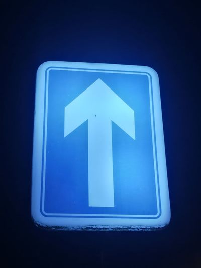 One way Black Background Illuminated Blue Road Sign Guidance Close-up Traffic Arrow Sign Street Name Sign One Way