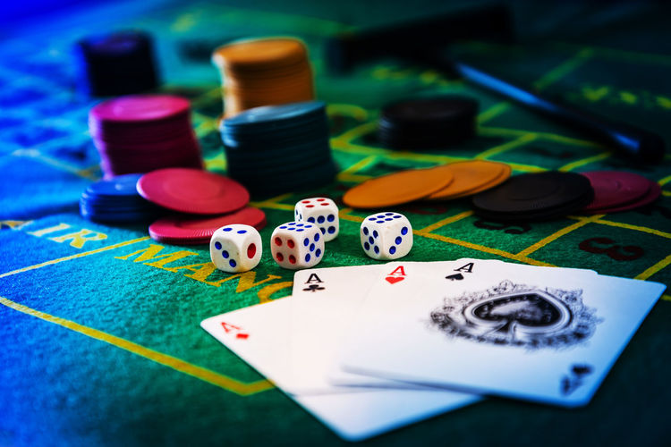Close-Up Of Cards With Gambling Chips And Dices On Table In Casino