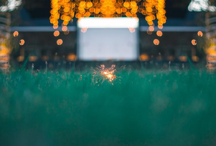 Blurred motion of sparkler against illuminated lighting equipment