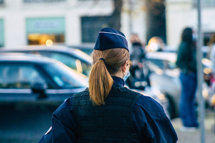Rear view of man standing on street in city