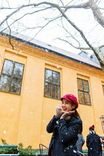 Portrait Of Smiling Woman Standing Against Building During Snow Fall