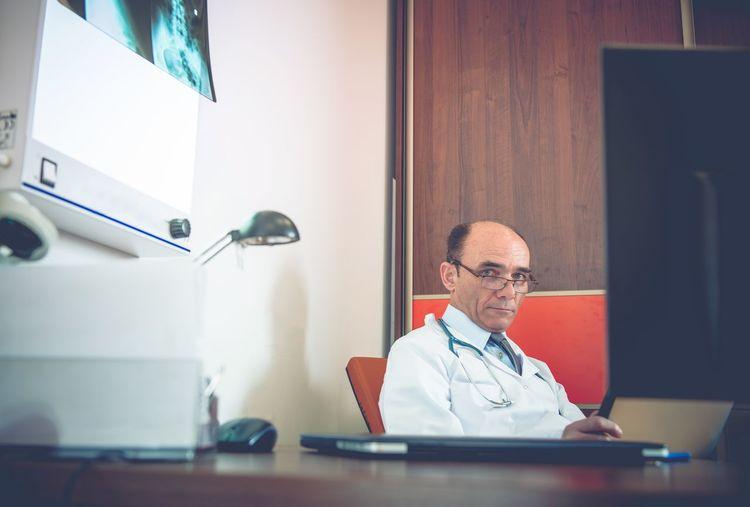 Portrait Of Doctor Sitting At Desk In Hospital