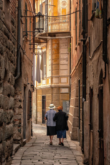 2 old ladies walking in the small streets of Ivrea, Italy Ivrea Laundry Old Town Adult Alley Architecture Italy Real People Rear View The Way Forward Togetherness Town Two People Walking Women Passageway Diminishing Perspective TOWNSCAPE Historic Cobblestone Housing Settlement Narrow Friend