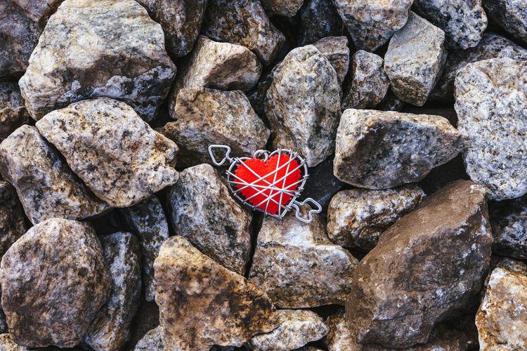 High angle view of heart shape stone on rock