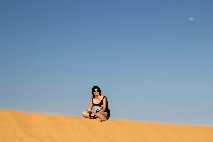 Happy woman resting on sand against clear blue sky