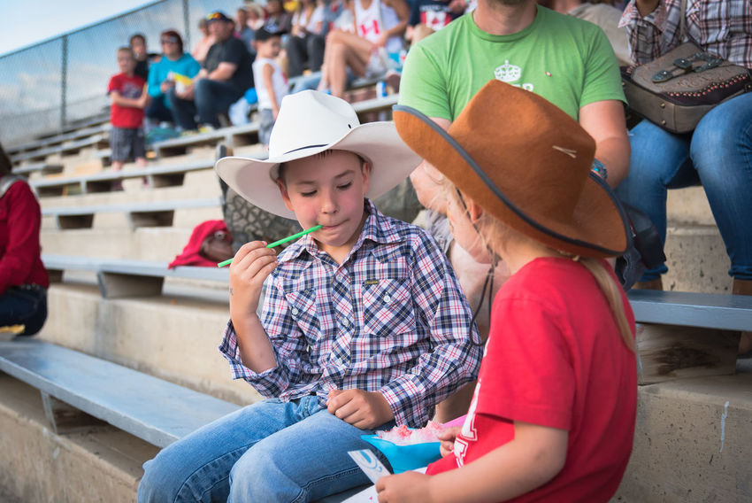 Williams Lake, British Columbia/Canada - July 1, 2016: two children enjoy a snow cone while watching the 90th Williams Lake Stampede, one of the largest stampedes in North America 90th Williams Lake Stampede Arena Children Event July Kids Rodeo Williams Lake Stampede Park Young Audience Canada Day Country Western Cowboy Hats  Crowd Cute Editorial  Evening Group Outdoors People Snow Cone Stampede Stampede Grounds Stands Summer
