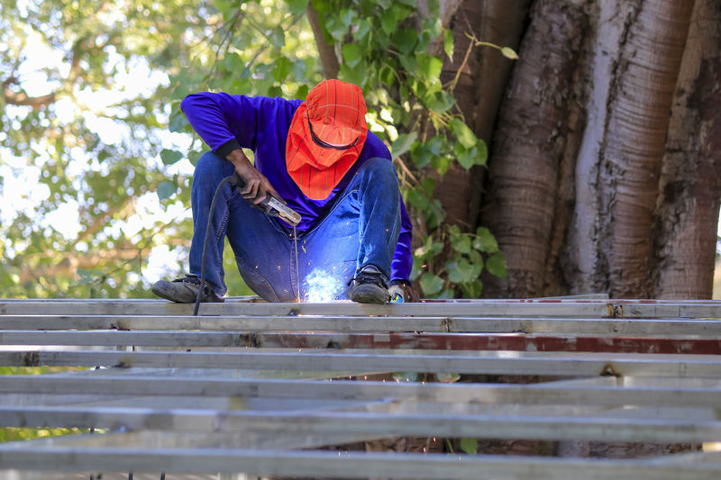 Man working on wood against trees
