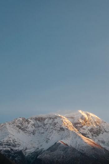 Snow capped mountain in karakoram range against blue sky. sunset at nagar valley, gilgit, pakistan.