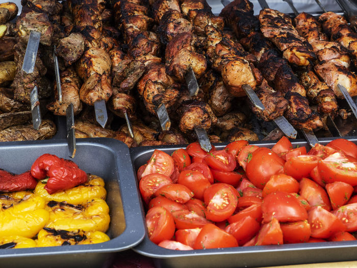 High angle view of meat in skewers with vegetables in container at market stall