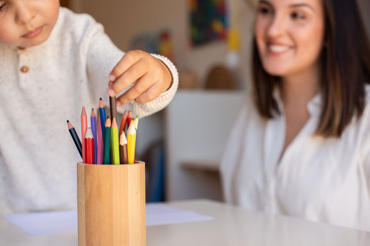 Portrait of woman holding pencils at home