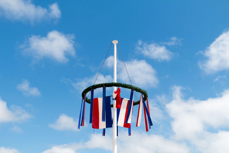 Festive wreath with little flag in front of blue sky Amusement Park Amusement Park Ride Arts Culture And Entertainment Blue Cloud - Sky Consumerism Day Flag Fun Hanging Low Angle View Metal Multi Colored Nature No People Outdoor Play Equipment Outdoors Pole Red Sky Sunlight