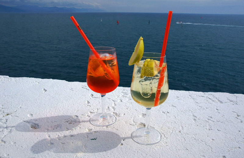 Drinks in glass on retaining wall against sea