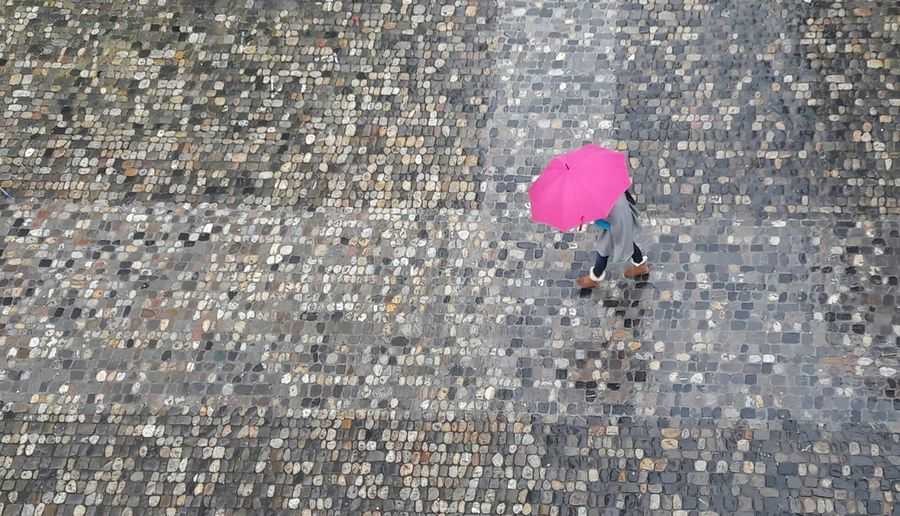 Think pink :-) Rainy Days Umbrella Pink Umbrella Pink Color High Angle View Outdoors Day Women One Person Cobblestones Streetphotography Wet April Nature Weather Weather Photography Rain City Pavedstreet Konstanz Street Photography The Street Photographer - 2017 EyeEm Awards