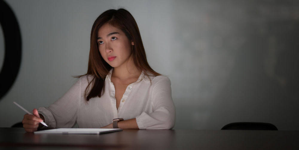 Businesswoman working while sitting on table