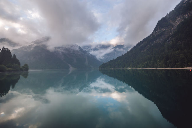 Beautiful scenic view of Lake Plansee on a moody autumn morning, Tirol, Austria Plansee Beauty In Nature Cloud - Sky Day Idyllic Lake Moody Mountain Mountain Peak Mountain Range Nature No People Non-urban Scene Reflecion Reflection Reflection Lake Scenery Scenic View Scenics - Nature Sky Symmetry Tranquil Scene Tranquility Water Waterfront