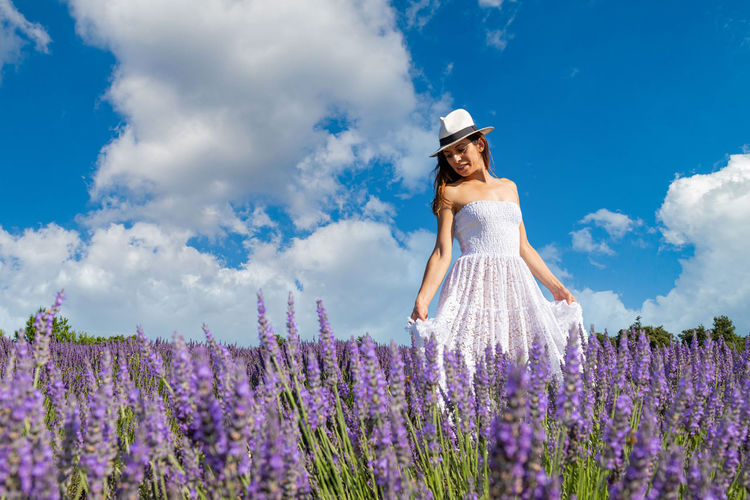 Young woman walking in a blooming lavender field. she wears a long white dress and a straw hat.