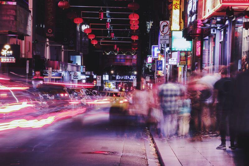 Blurred Motion Of People On Sidewalk At Night