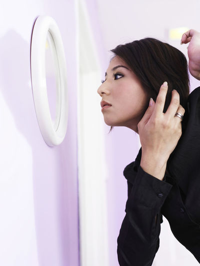 Side View Of Woman Adjusting Hair While Looking In Mirror