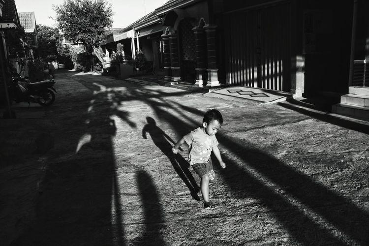 Girl walking on footpath in city