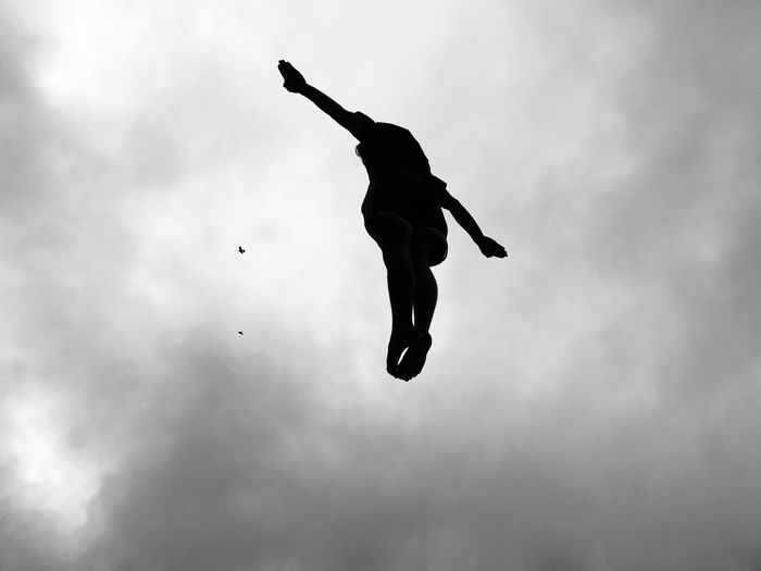 Low angle view of silhouette person jumping against sky
