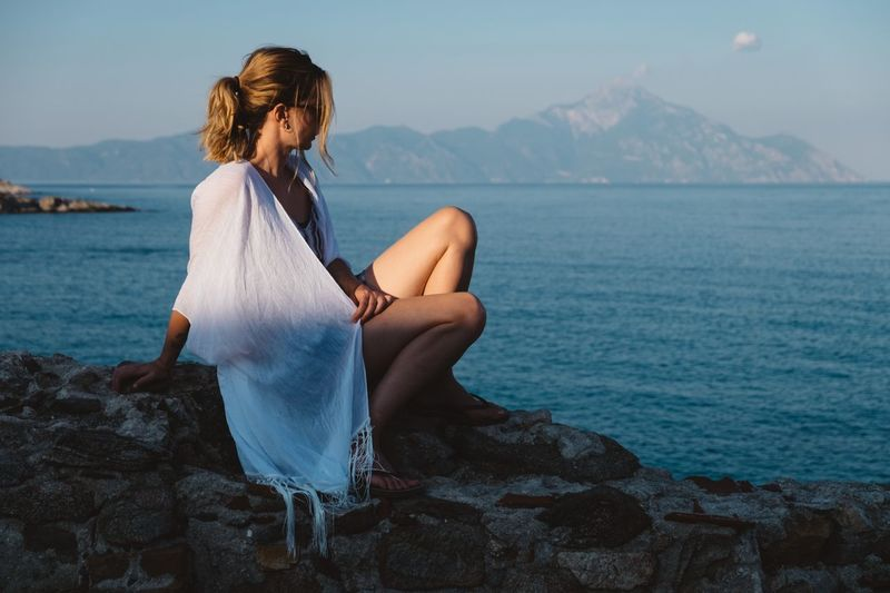 EyeEm Selects One Person Sea Real People Young Adult Full Length Rock - Object Water Mountain Young Women Rear View Leisure Activity Standing Lifestyles Sitting Outdoors Long Hair Nature Women Beauty In Nature Beautiful Woman The Week On EyeEm