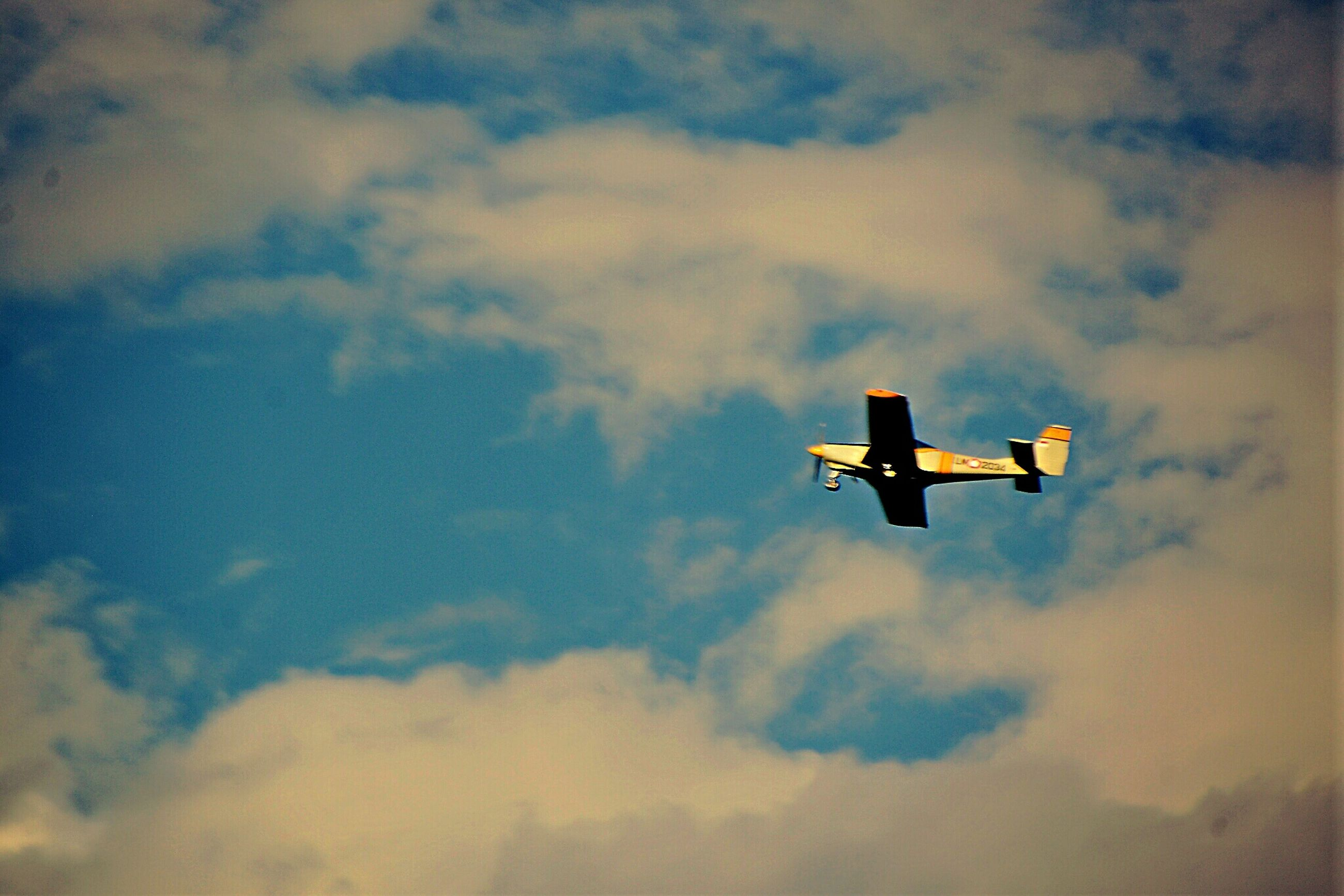 low angle view, sky, flying, cloud - sky, airplane, silhouette, mid-air, air vehicle, cloudy, lighting equipment, cloud, street light, dusk, sunset, outdoors, no people, nature, transportation, bird, weather
