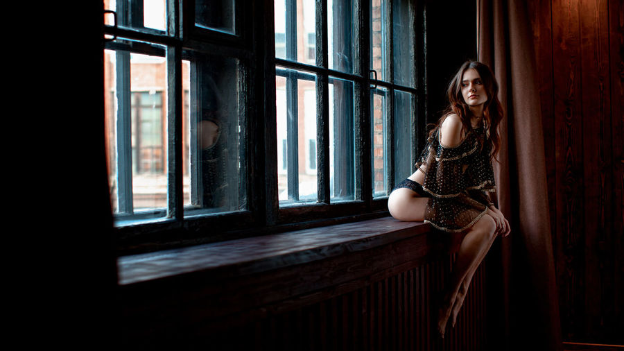 Thoughtful young model wearing lingerie while sitting on window sill at home