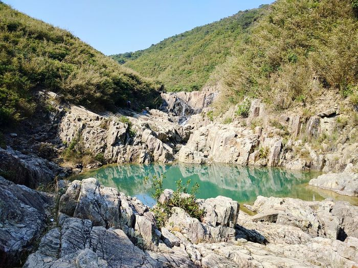 Scenic view of hot spring amongst rock formations