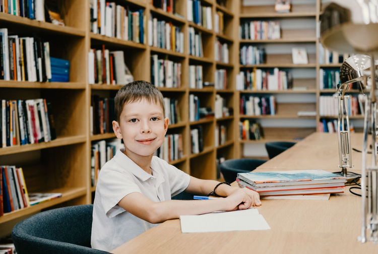 The boy sits in the library and writes in a notebook at the table. preparing for homework.