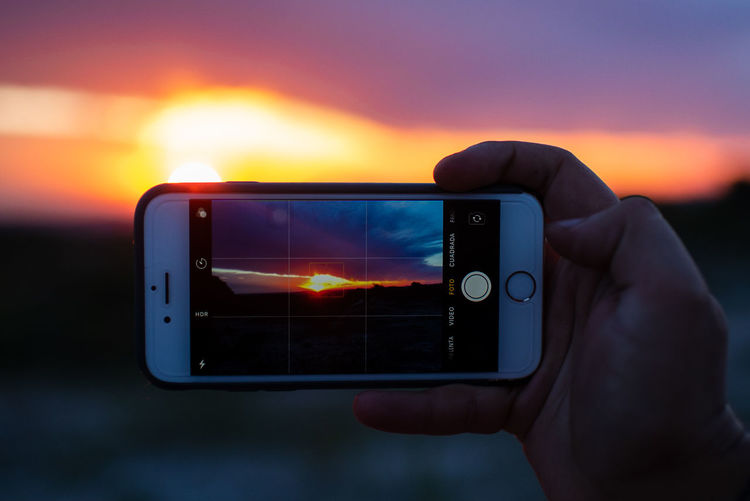 Technology Photography Themes Wireless Technology Sunset Smart Phone Photographing Portable Information Device Communication Screen Holding Mobile Phone Activity Sky Human Hand Device Screen Hand Human Body Part Connection Nature One Person Digital Camera Outdoors Humanity Meets Technology