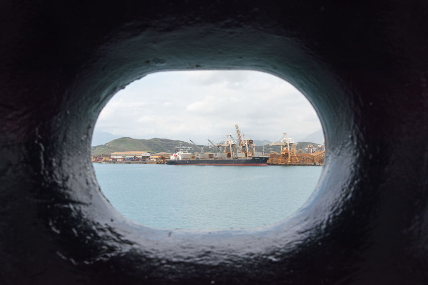NOUMEA, NEW CALEDONIA-NOVEMBER 25,2016: View through port hole of commercial dock with cranes, sea containers and container ship in Noumea, New Caledonia Container Ship Gantry Cranes Noumea Shipping Containers Transportation Architecture Building Exterior City Cityscape Crane Day Dockside Freight Transportation Nature Nautical Vessel New Caledonia Pacific Ocean Sea Sea Container Ship Shipping  Shipyard Sky View Through Water