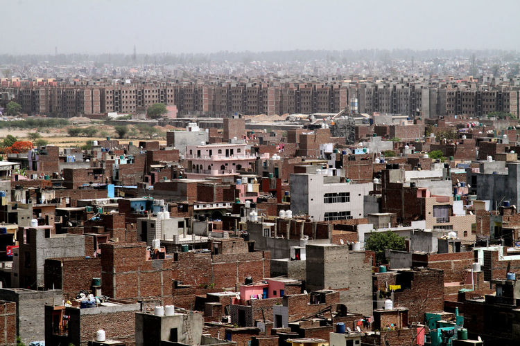 High angle view of buildings in city, unauthorised colony and new high rise building construction.