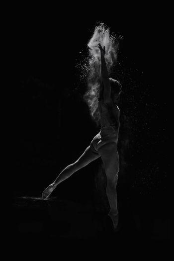 Ballet dancer dancing against black background