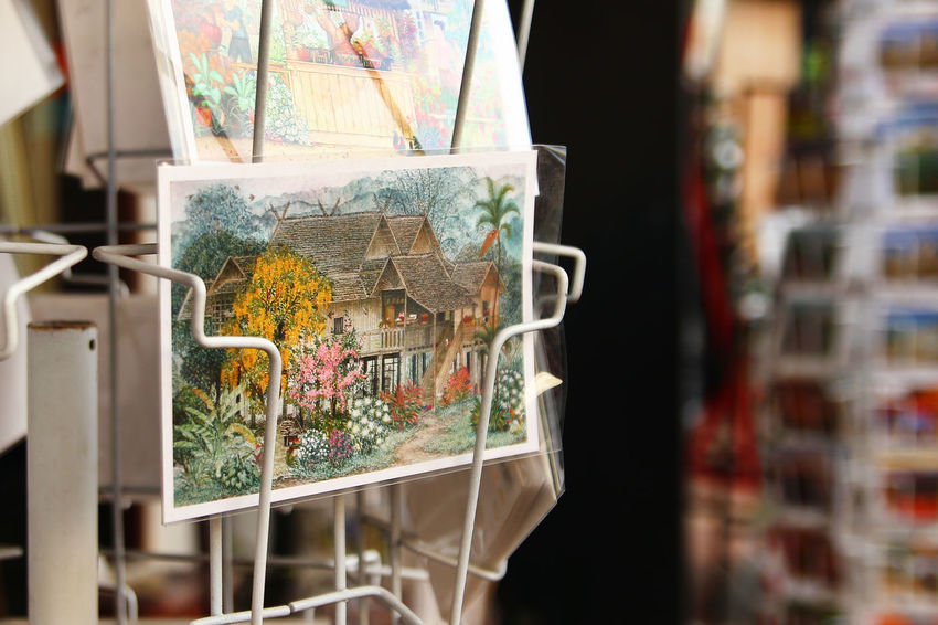 Painted postcards for tourists on a shop window in a souvenir shop. Painted Postcard Receive Sending A Letter Shopping Travel Art And Craft Book Choice For Sale Indoors  Memory Multi Colored No People Postbox Reflection Retail  Retail Display Selective Focus Shelf Souvenir Store Tourism Transparent Variation